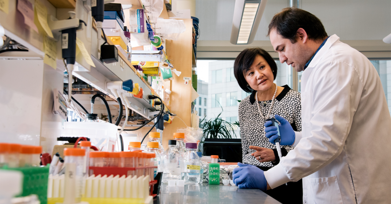 Two neuroscientists stand at a lab bench. One, wearig gloves and a white coat, works with a pipette