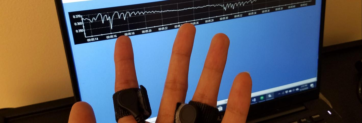 A hand with black bands strapped around the pointer and ringer is shown in front of a computer screen with a wiggly line stretching across
