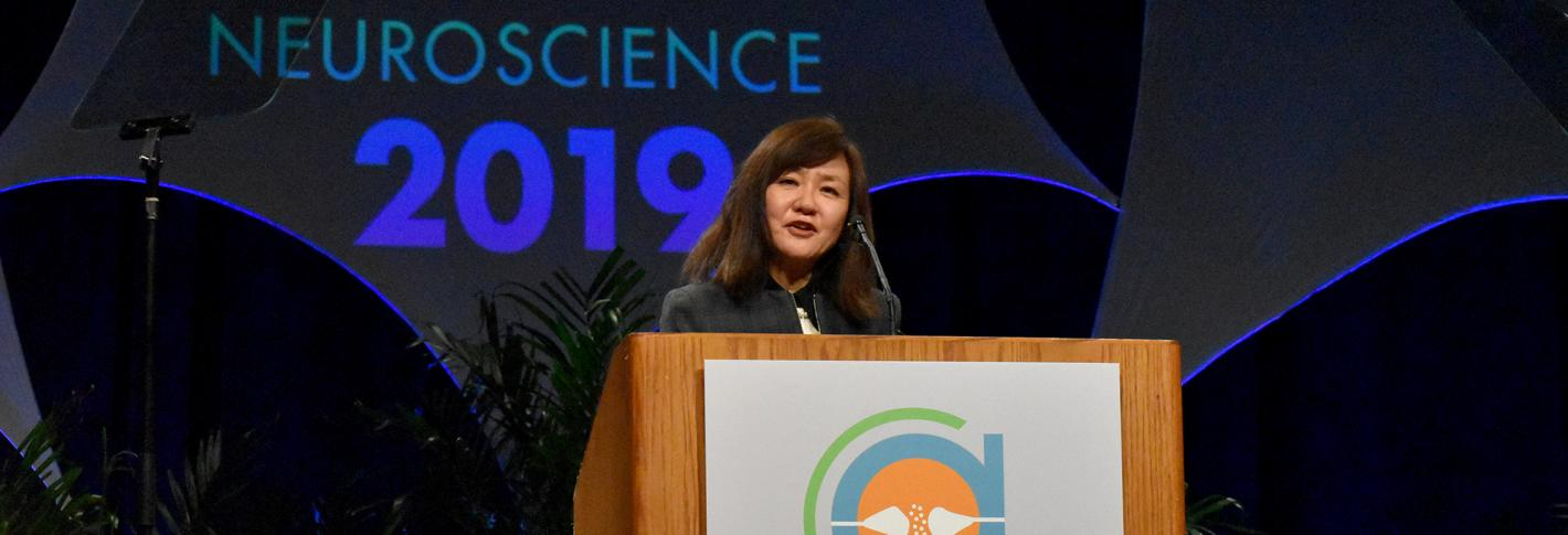 Li-Huei Tsai speaks from the podium with a huge Neuroscience 2019 sign behind her