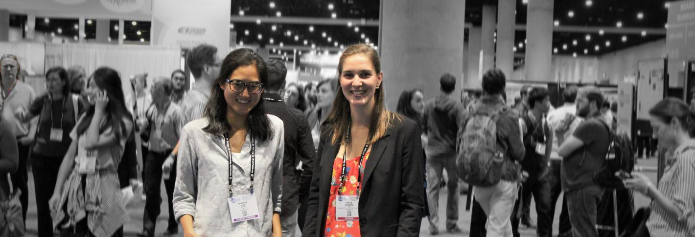 Two picower researchers are highlighted in color before a backdrop of the conference show floor, which is blurred and grayscale