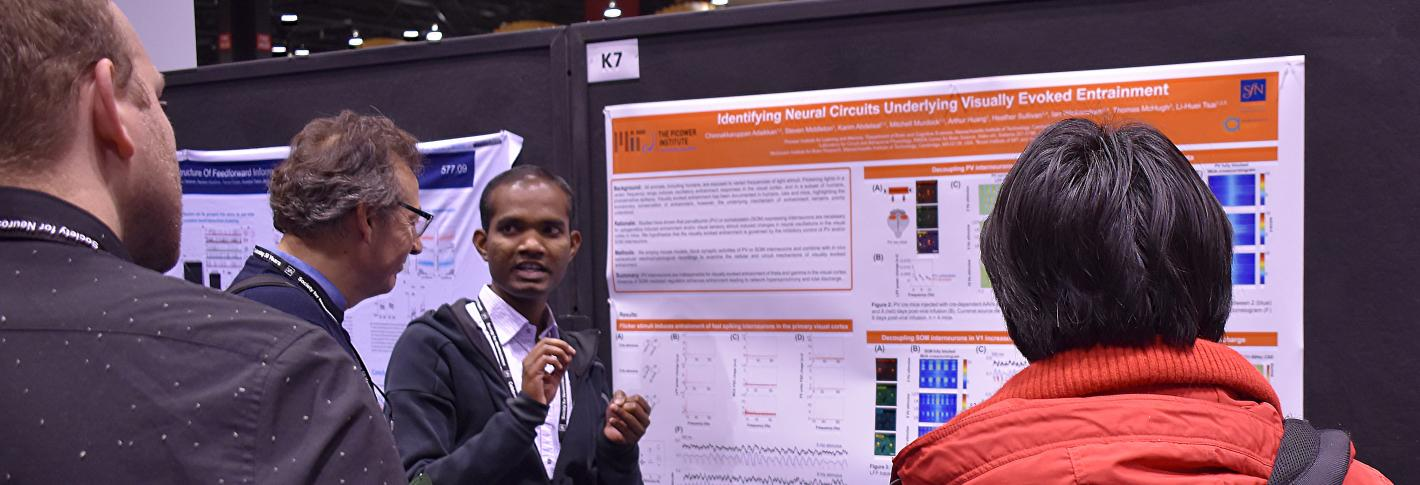 Chinna Adaikkan gestures as he stands at his research poster explaining it to three onlookers