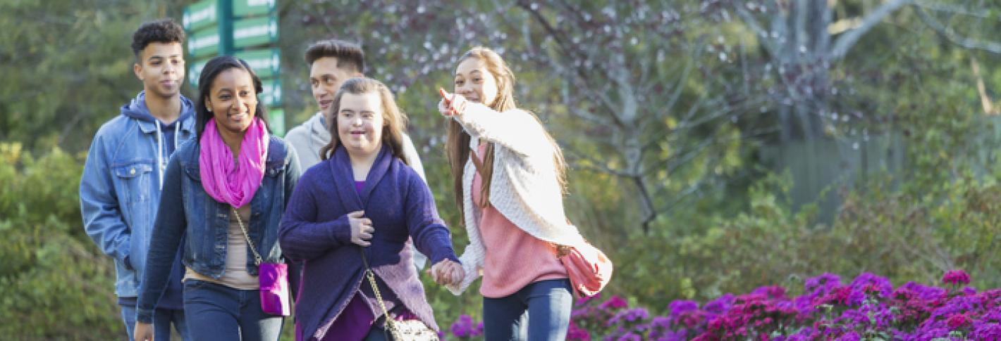 A teen girl with down syndrome walks through a park with friends