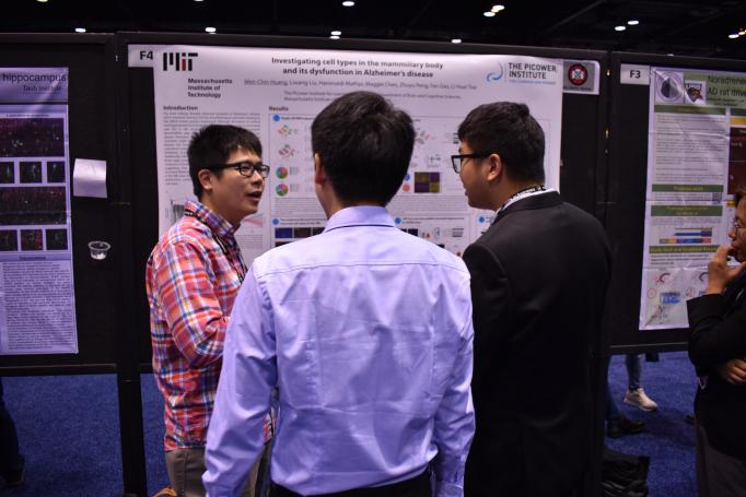 Wen-Chin Huang gestures as he presents his poster to two onlookers