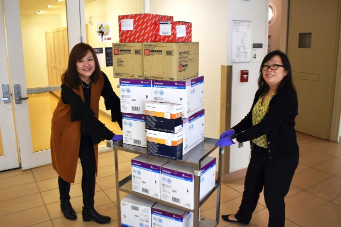 Two women push a rolling cart full of boxes of biomedical supplies