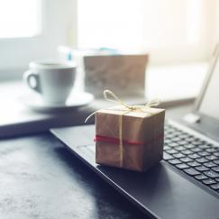 A small present wrrapped in brown paper and twine sits atop a laptop on a desk