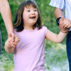A girl with Down syndrome smiles while she holds her parents' hands.