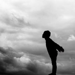 Silhouette of a child leaning toward a dark cloudmass, as if blowing the dark clouds away