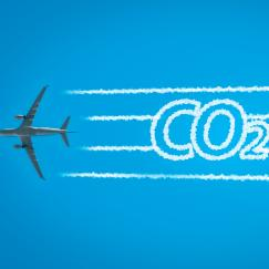 An airplaine seen  from below extends contrails that take the form of the letters CO2