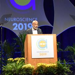 Emery Brown speaks at the SfN podium with flowers on the stage below