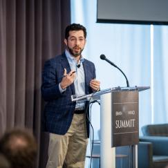 Ed Boyden stands and gestures at the podium of the Brain Mind Summit