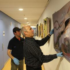 Todd Siler holds a painting up against a wall while an installer helps him assess its placement