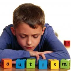 A boy sits with letter blocks that spell AUTISM